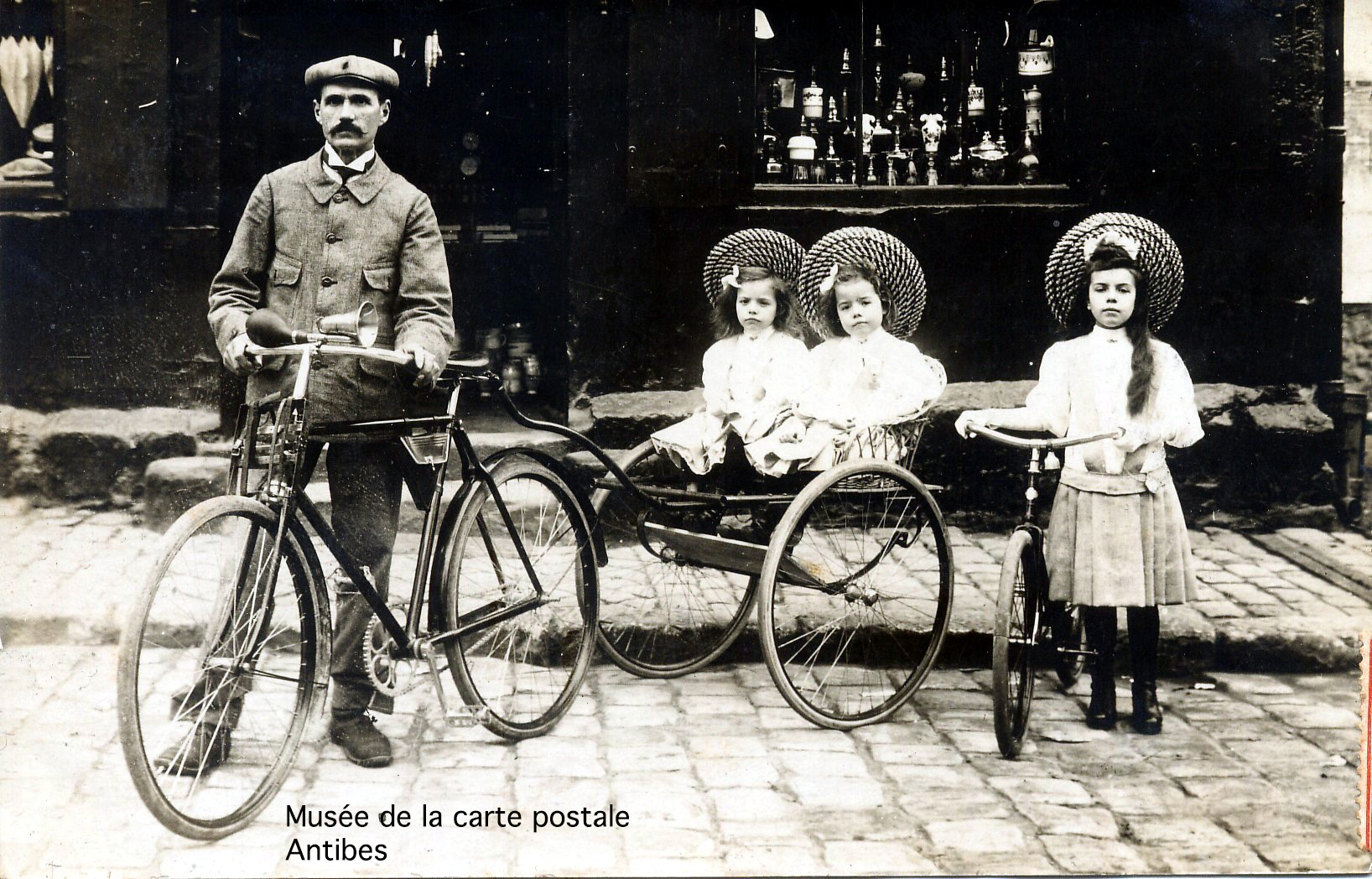 Carte postale ancienne représentant le vélo comme moyen de transport pour la famille.