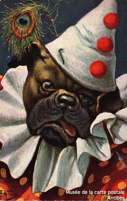 Carte postale ancienne représentant un chien habillé en Pierrot la Lune, issue de l'exposition temporaire sur les animaux humanisés, au Musée de la Carte Postale, à Antibes.