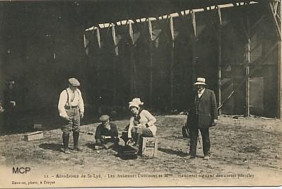 Carte postale à valeur documentaire, représentant des aviateurs dédicaçant des cartes postales.