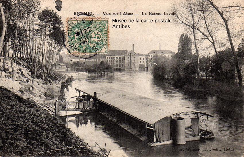Carte postale ancienne représentant le bateau-lavoir de Rethel, sur l'Aisne, issue de l'exposition temporaire du musée de la Carte Postale.