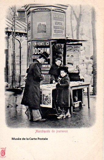 Carte postale ancienne représentant un des anciens kiosques à journaux, et sa marchande.