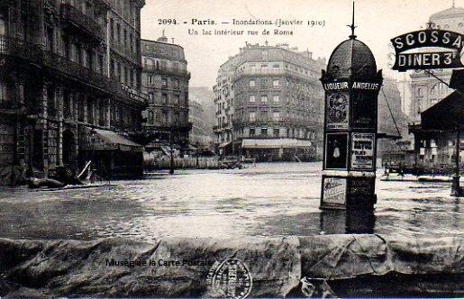 Carte postale ancienne représentant un kiosque à journaux de la rue de Rome à Paris, pendant les inondations de 1910.