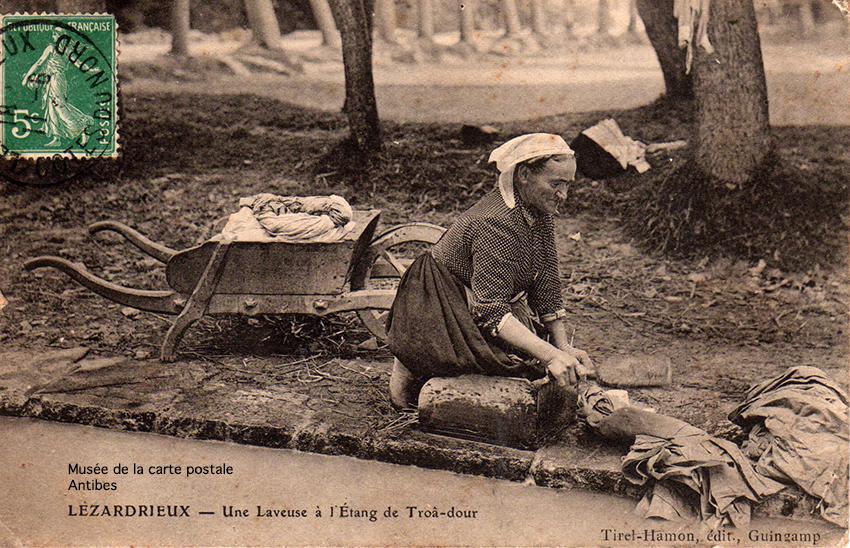 Carte postale ancienne représentant une lavandière, laveuse sur au bord de l'étang du Troa-Dour à Lézadrieu, issue de l'exposition temporaire du musée de la Carte Postale.