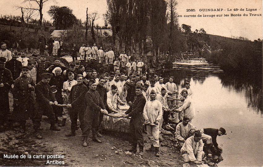 Carte postale militaire ancienne représentant des hommes durant la corvée du lavage sur les bords du Trieux à Guingamp, issue de l'exposition temporaire du musée de la Carte Postale.