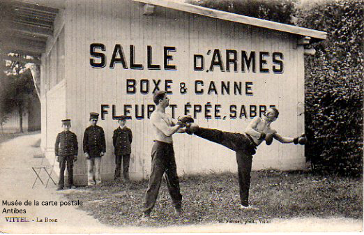 Carte postale illustrant une salle d'armes de Boxe Française et canne, issue de l'exposition temporaire présentée par le Musée de la Carte Postale, à Antibes.