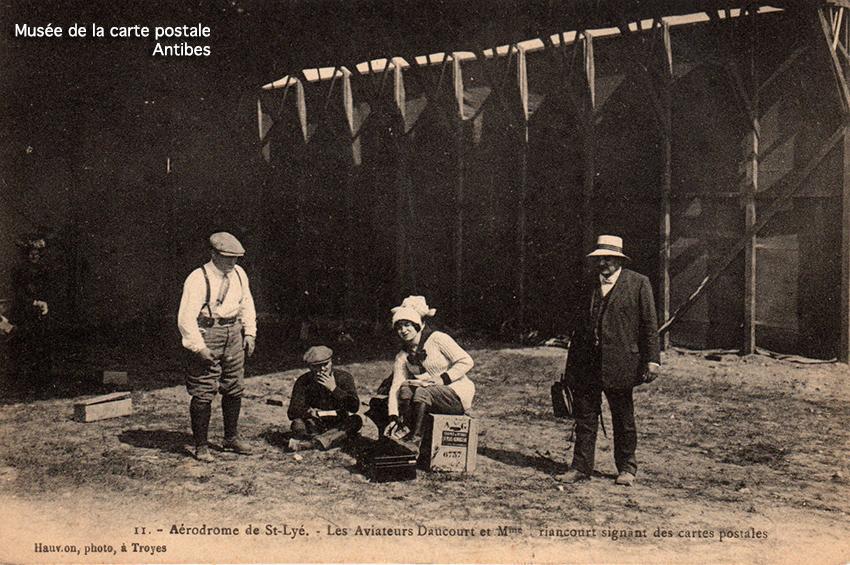Carte postale ancienne représentant les aviateurs Daucourt et Driancourt signant des autographes sur cartes postales dans l'aérodrome de Saint Lyé.