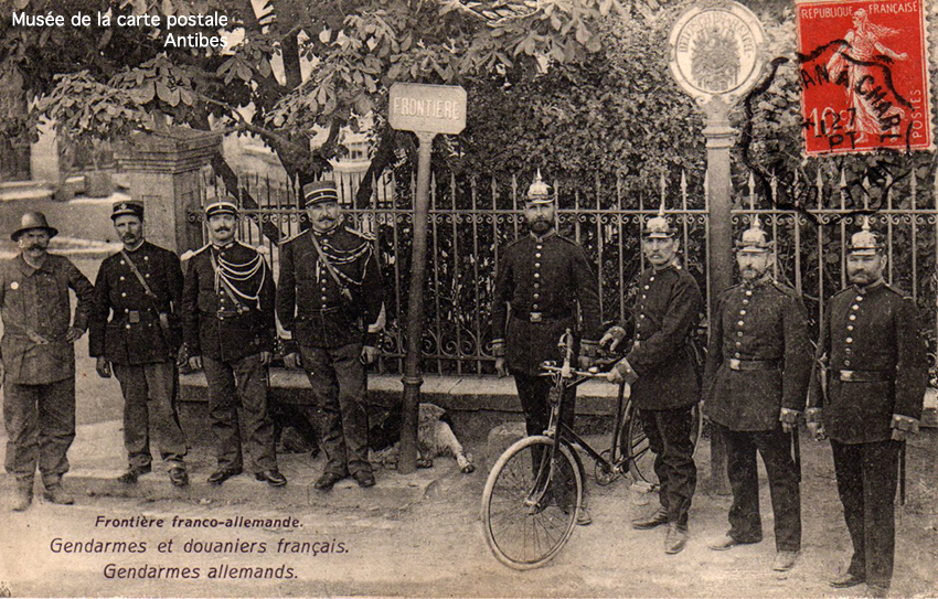 Carte postale ancienne représentant un poteau à la frontière franco-allemande avec des gendarmes et douaniers.