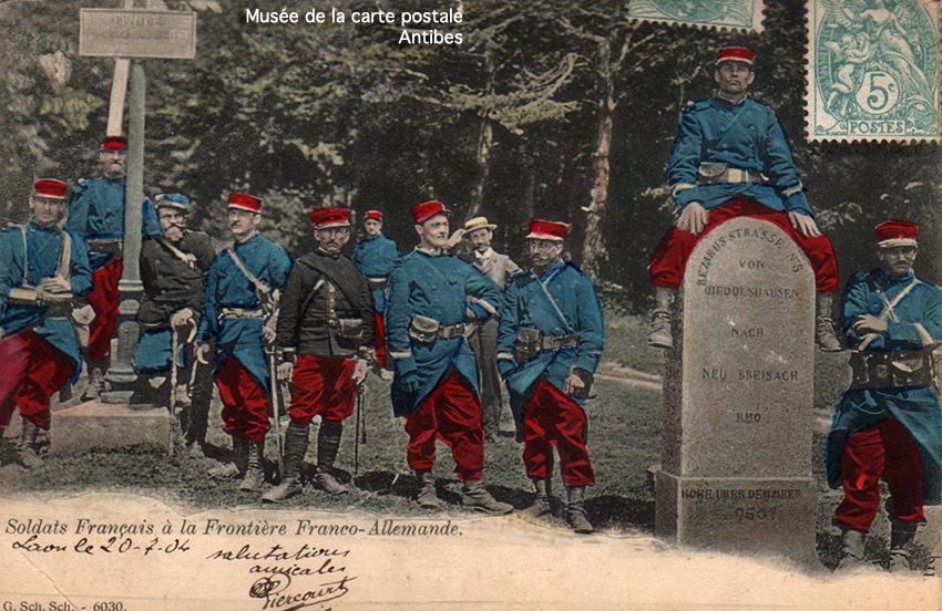 Carte postale ancienne représentant un poteau à la frontière franco-allemande avec des soldats.