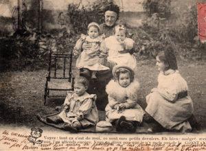 Carte postale ancienne représentant une grand-mère et ses petits-enfants.