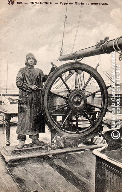 Carte postale ancienne représentant un marin au gouvernail, issue de l'exposition des grands voiliers au Musée de la Carte Postale, d'Antibes.