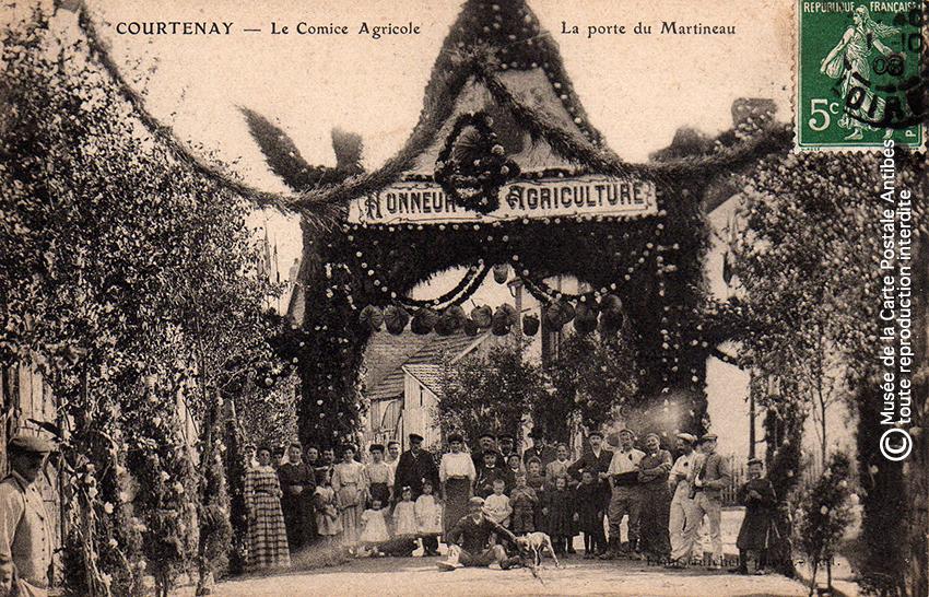 Carte postale représentant un arc de triomphe du comice agricole à Courtenay, issue de l'exposition temporaire sur les Arcs de triomphe au Musée de la Carte Postale.