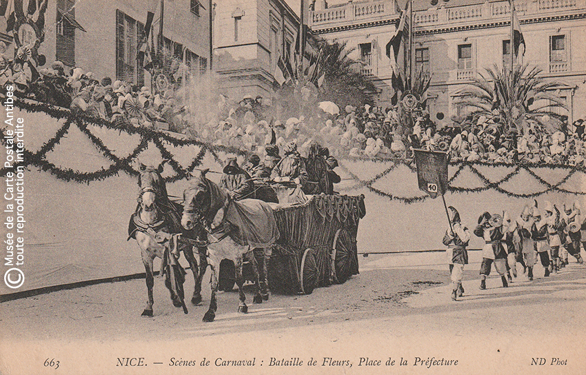 Carte postale ancienne représentant une bataille de fleurs sur la Place de la Préfécture lors du Carnaval de Nice, issue des réserves du Musée de la Carte Postale situé à Antibes.