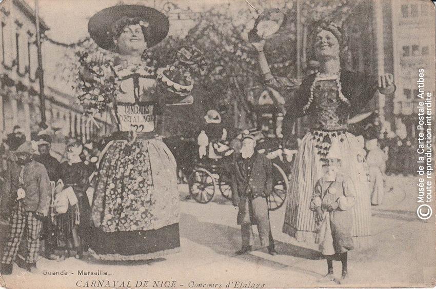 Carte postale ancienne représentant un concours d'étalage de grosses têtes au carnaval de Nice, issue des réserves du musée de la carte postale situé à Antibes.