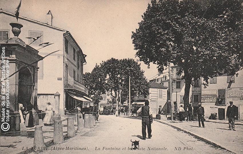 Carte postale ancienne représentant la fontaine et la route nationale de La Turbie.
