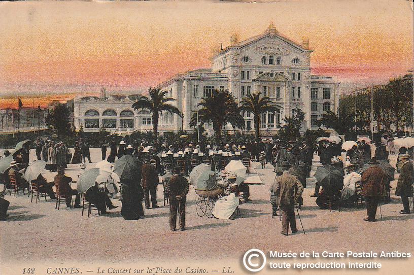 Carte postale ancienne représentant un concert sur la place du casino municipal de Cannes, issue des réserve du musée de la carte postale, à Antibes.